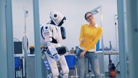 Робот и человеческие отношения Киборг шлепает женщину, пока танцующ, тогда она шлепает свою сторону и выходит 4K акции видеоматериалы