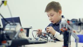 Робот мальчика студента собирая в классе школы robotechnics Концепция образования инженера акции видеоматериалы