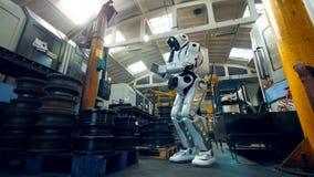 Робот проверяет части металла на фабрике, работая с планшетом сток-видео