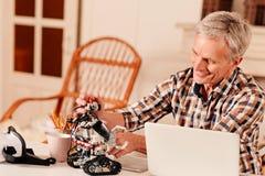 Робот старшего инженера рассматривая пока работающ на компьтер-книжке стоковое изображение rf