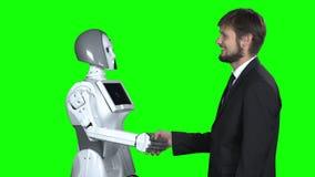 Робот трясет руки с парнем приветствует его зеленый экран сток-видео