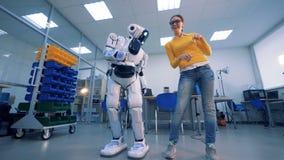 Робот шлепает женщину на батокс, тогда она дает ему шлепок 4K акции видеоматериалы