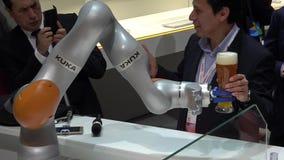 Робот Kuka подготовляет лить пиво на ярмарке в Ганновере, Германии Messe сток-видео