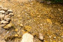 Ровная вода с камнями на дне Стоковое Фото