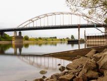 Ровная вода смотря прошлые утесы на мосте через реку Стоковое Изображение