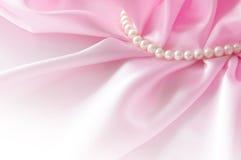 Ровная элегантная розовая silk предпосылка с жемчугом, красивый шелк задрапировывает Стоковое Изображение RF