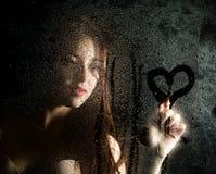 Ровный портрет сексуальной модели, представляя за прозрачным стеклом предусматриванным падениями воды и рисует сердце на стекле стоковые изображения