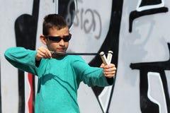 Рогатка стрельбы ребенк на предпосылке граффити Стоковые Фотографии RF