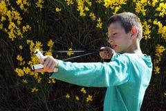 Рогатка стрельбы ребенк на предпосылке кустарника Стоковое Изображение RF