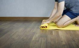 Рогожка человека циновка йоги дома стоковое изображение