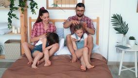 Родители делают массаж для 2 дочерей, сидят на кровати, смехе и иметь полезного время работы акции видеоматериалы