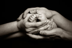 Родители держа ноги их ребенка нежно Стоковые Фото