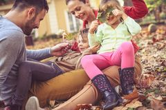 Родители играя при маленькие девочки, сидя на земле Море осени Стоковые Изображения