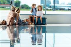 Родители и дети ждать восхождение на борт в авиапорте стоковое изображение rf