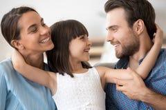Родители счастливого смешного объятия ребенк молодые ослабляя дома стоковые изображения