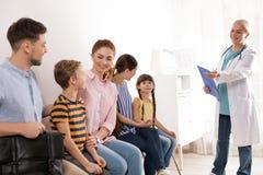 Родители с детьми ждать их поворот Посещая доктор стоковая фотография rf