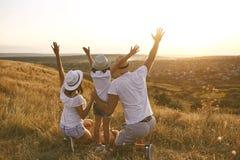 Родители с ребенком смотря, что ослабить на заходе солнца на природе лета стоковое фото