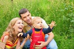 родители травы ребенка сидят Стоковая Фотография