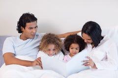 Родители читая книгу с их дет Стоковые Фотографии RF
