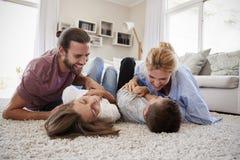 Родители щекоча детей по мере того как они играют игру в салоне совместно стоковое изображение