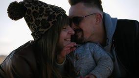 Родительское объятие для ребенка в солнечном свете, женатой паре хорошего настроения молодой с сыном в tof под открытым небом, сч сток-видео