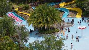 Родитель и дети наслаждаясь скольжениями и бассейном на Aquatica