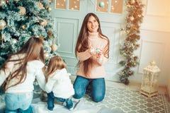 Родитель и 2 дет имея потеху и играя совместно около рождественской елки Стоковое Фото
