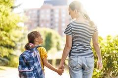 Родитель и зрачок идут к школе стоковое фото