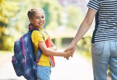 Родитель и зрачок идут к школе стоковое фото rf