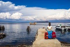 Родная женщина боливийских Анд, в палубе с красными сумками и шлюпке totora в озере Titicaca, Боливия Стоковые Изображения