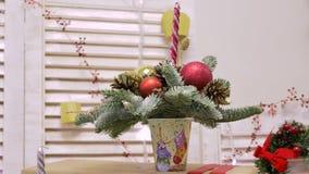 Рождественская елка в стекле, украшенном с пестроткаными шариками, конусами и свечами видеоматериал