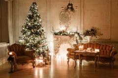 Рождественская елка, гирлянды, свечи, фонарики, подарки в вечере классический интерьер белой украшенной комнаты с стоковая фотография