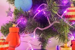 Рождественская елка зарева с висеть декоративный орнамент для приветствия сезона Стоковые Изображения