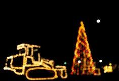 Рождественская елка и бульдозер/трактор запачканные/bokeh украшенный с светами Стоковые Изображения RF