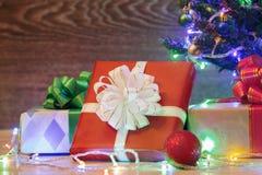 Рождественская елка на деревянной предпосылке с гирляндой и подарками Стоковое фото RF