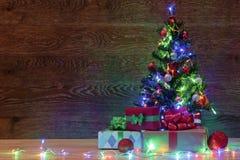 Рождественская елка на деревянной предпосылке с гирляндой и подарками Стоковые Изображения RF