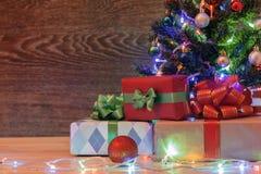 Рождественская елка на деревянной предпосылке с гирляндой и подарками стоковая фотография rf