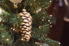 Рождественская елка с праздничными золотыми конусами и света с космосом экземпляра на запачканной предпосылке bokeh в моле xmas в Стоковые Изображения