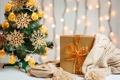 Рождественская елка украсила снежинки и гирлянду, подарок с связанным шарфом на предпосылке bokeh и белые доски весело стоковые изображения