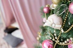 Рождественская елка украшенная с игрушками в серебряном и розовом цвете В ем мы видим воздушные шары с лентами и светами Стоковая Фотография RF