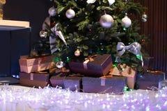 Рождественская елка, fairy света и подарочные коробки внутри помещения Стоковые Фото