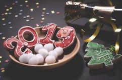 Рождественская открытка: на деревянной плите печенья красного имбиря в форме 2019 и белые круглые снежинки стоковое фото rf