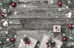 Рождественская открытка, на старой деревянной предпосылке Подарки, красные шарики и handmade игрушки Космос для текста Взгляд све стоковая фотография rf