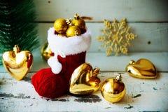 Рождественская открытка с красными орнаментом и оформлением ботинка Санты на Snowy w Стоковая Фотография