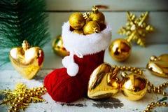 Рождественская открытка с красными орнаментом и оформлением ботинка Санты на предпосылке Snowy деревянной Селективный фокус с кос Стоковая Фотография