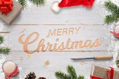 Рождество высекая в белой деревянной доске С Рождеством Христовым текст приветствию окруженный с украшениями Стоковое фото RF