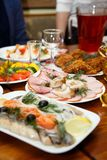 Рождество Комплект таблицы, взгляд со стороны Мяс на таблице праздника Отрезанные посоленные сельди на белой плите с травами, лим Стоковые Фото