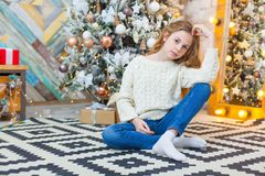 Рождество красивейший усмехаться девушки сидит над предпосылкой светов рождественской елки счастливое Новый Год Стоковые Изображения