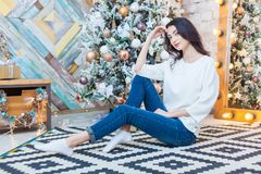 Рождество красивейший усмехаться девушки сидит над предпосылкой светов рождественской елки счастливое Новый Год Стоковые Фотографии RF