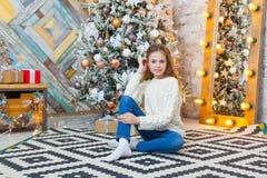 Рождество красивейший усмехаться девушки сидит над предпосылкой светов рождественской елки счастливое Новый Год Стоковое Фото